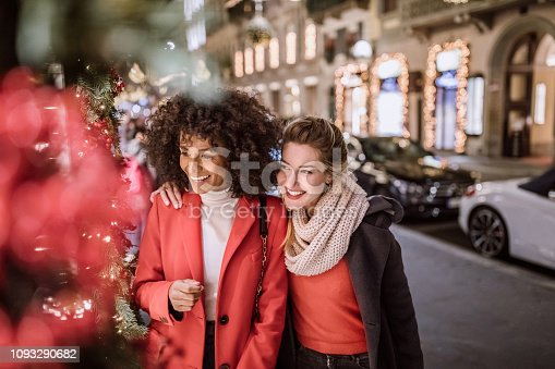 Two Fashionable And Attractive Young Women, Walking Together In Search For More Christmas Presents To Purchase