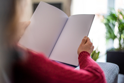 A woman is sitting on a couch in a living room and is holding a paper magazine in her hands. The publication is open and you can see two pages of the inside of the brochure. The pages are left blank for your own design ideas.
