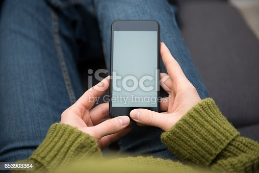 A blond young woman is sitting indoors at home and is holding a mobile phone in her hands. The device screen is left empty for your own telephone web page design or photograph. The photo was taken over the model's shoulder out of a rear view.