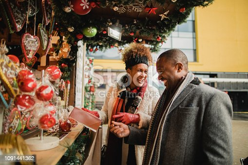 Mature couple looking at a Christmas market stall in a city centre. They are talking and laughing while holding a gift.