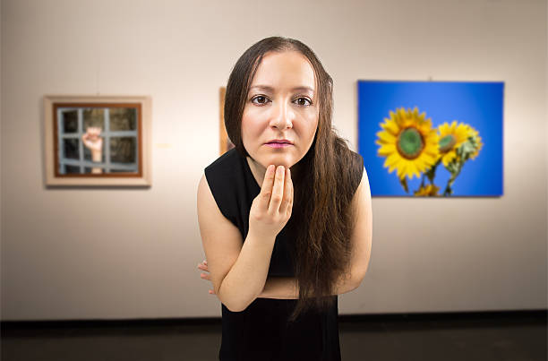 looking at a work of art Woman closely scrutinizing a painting at an exhibition of the museum.Background photos are my property critic stock pictures, royalty-free photos & images