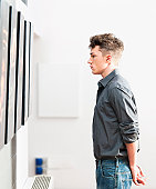 A young man looking at pictures on display in an art gallery.