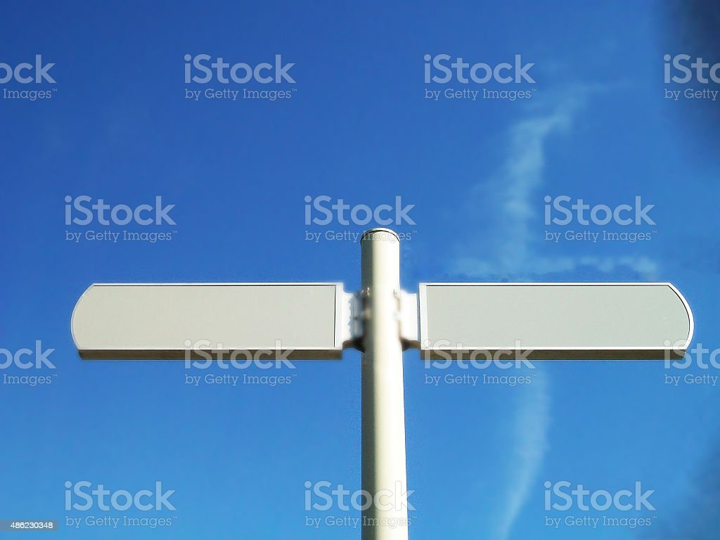 Looking At Blank Sign Post Against Summer Clear Blue Sky stock photo