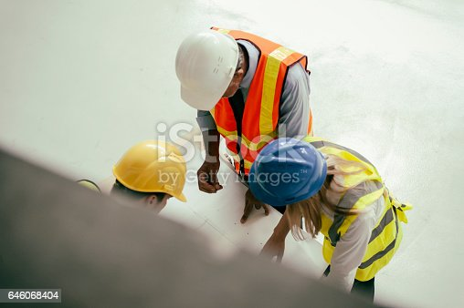 521012560istockphoto Looking at blueprints 646068404