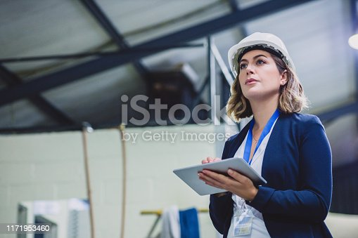 Cropped shot of a focused female engineer wearing safety gear while doing an inspection on machinery inside of a workshop