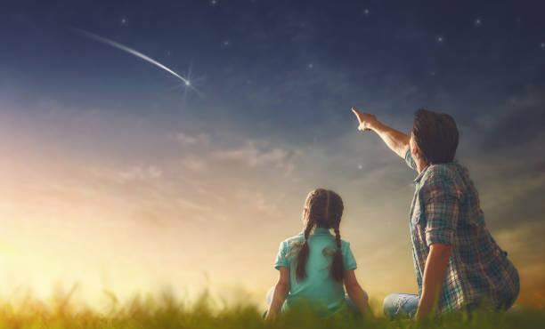 looking at falling star stock photo