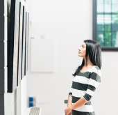 An attractive young woman looking at pictures on display in a gallery.\n\n[url=file_closeup.php?id=18597560][img]file_thumbview_approve.php?size=2&id=18597560[/img][/url] [url=file_closeup.php?id=20239509][img]file_thumbview_approve.php?size=2&id=20239509[/img][/url]