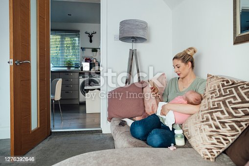 A young woman sitting on the sofa in her living room, holding her newborn baby in her arms while using her phone to check energy use in the home.