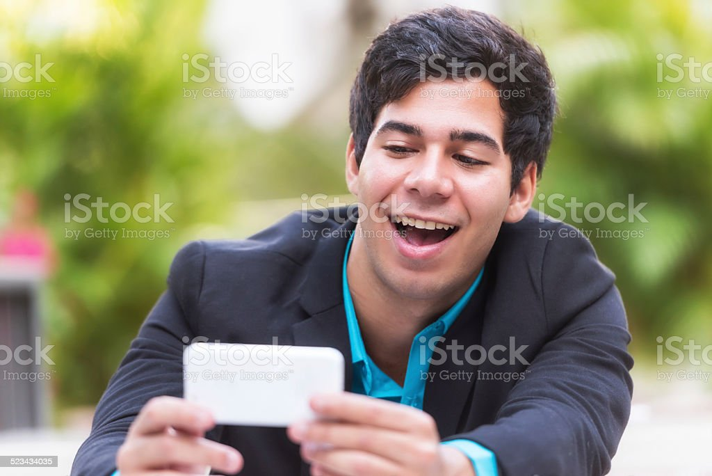 Looking at his smart phone stock photo