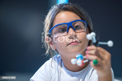 Young scientist looking at a molecular structure model.