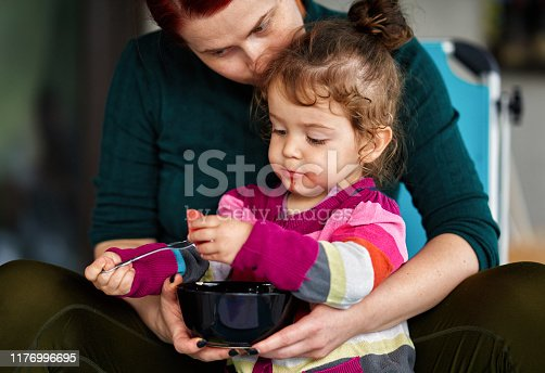 Mother holding her daughter while eating watermelon
