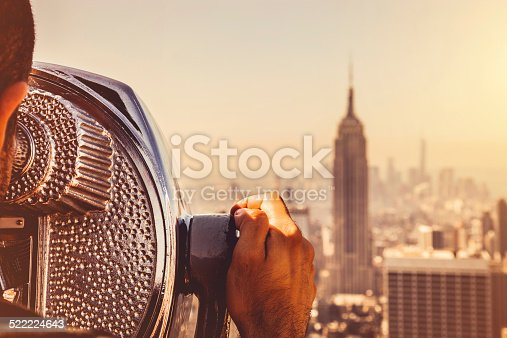 Looking at New York skyline, close up of an old binocular for tourists.