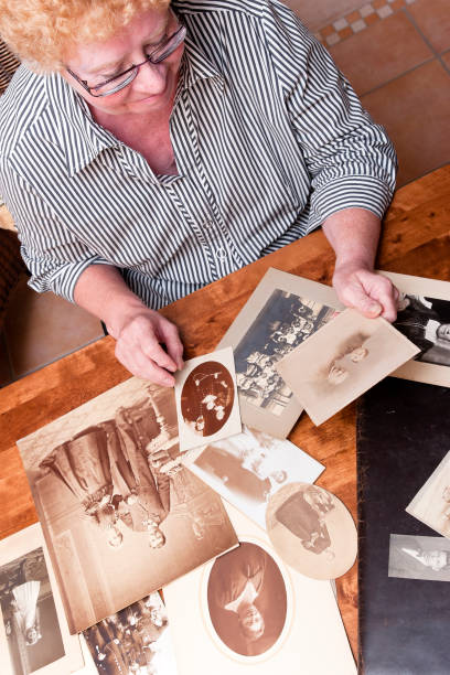 Looking at old Photo Album Senior woman looking at old Family Photos sentimentality stock pictures, royalty-free photos & images