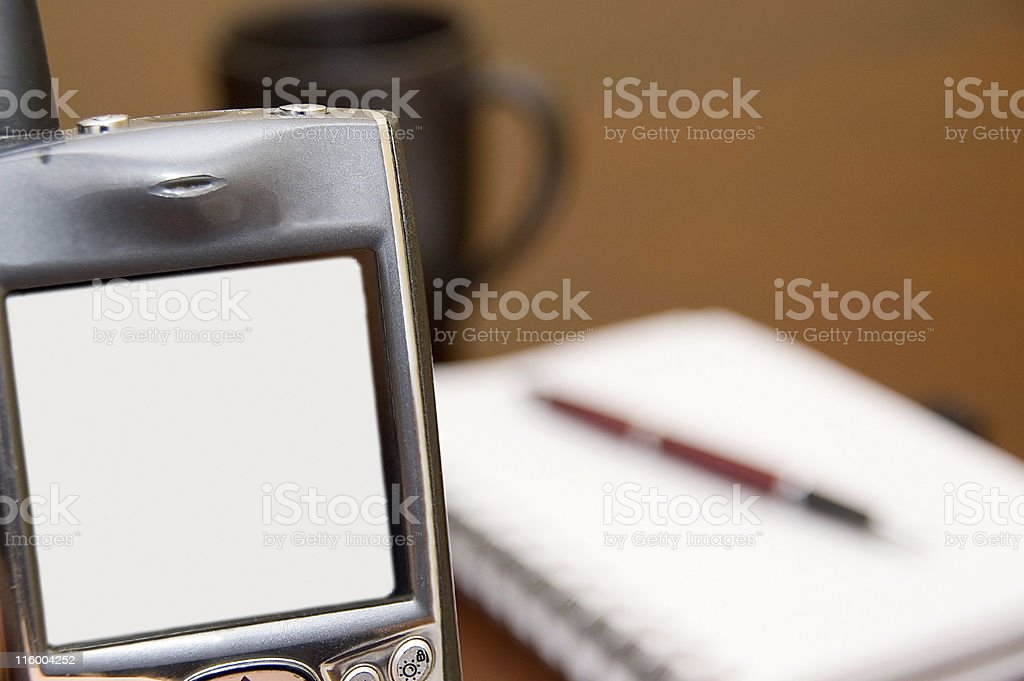 Looking at PDA Phone with a Notebook, Pen, and Coffee royalty-free stock photo