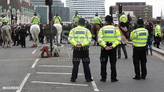 Scene Of Of British Metropolitan Police Officers Standing,Watching,Mounted Police Officers Looking Around At So Many People,People Standing,Looking Around,Taking Pictures,Talking To One Another,Holding Protest Banner During The March 2017 Terrorist Attack Anniversary Which Took Place At Westminster London England Europe