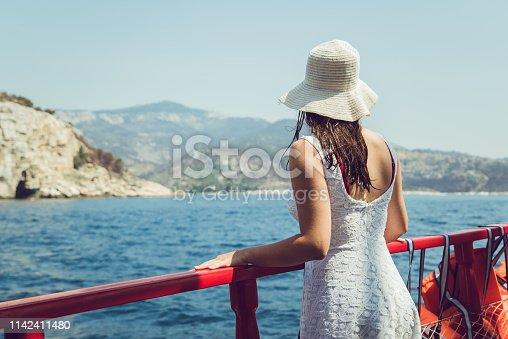 Elegant, young female on a thrilling boat ride, enjoying summer sun. Thassos island, Greece.