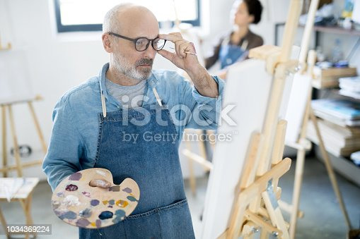 istock Looking at sketch on easel 1034369224