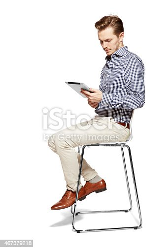Studio shot of surprised man looking at tablet.