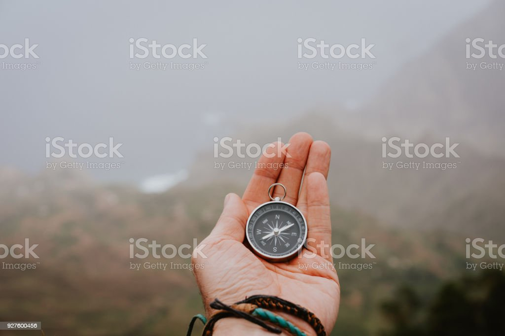 Looking at the compass to figure out right direction. Foggy valley and mountains in background. Santo Antao. Cape Cabo Verde - Zbiór zdjęć royalty-free (Bieg na orientację)