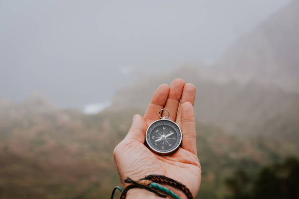 Looking at the compass to figure out right direction. Foggy valley and mountains in background. Santo Antao. Cape Cabo Verde stock photo