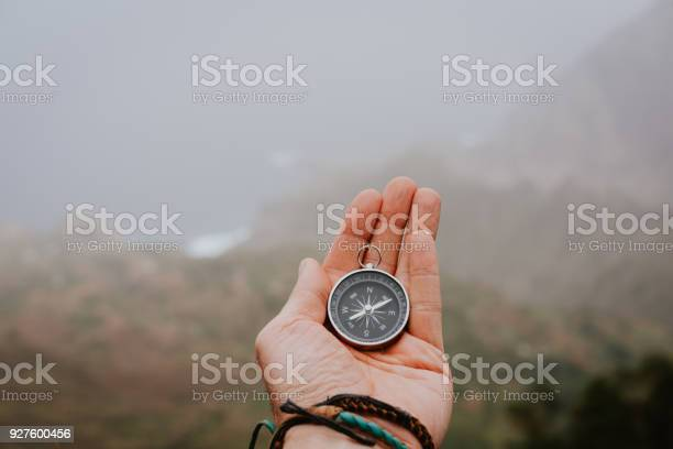 Photo of Looking at the compass to figure out right direction. Foggy valley and mountains in background. Santo Antao. Cape Cabo Verde