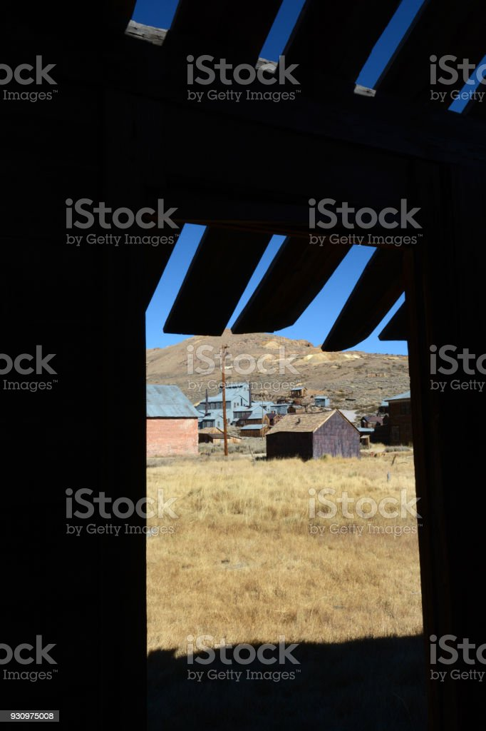 Looking at the ghost town of Bodie through a doorway of an abandoned building stock photo