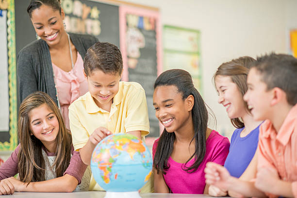 looking at the globe in geography class - middle school teacher stock pictures, royalty-free photos & images