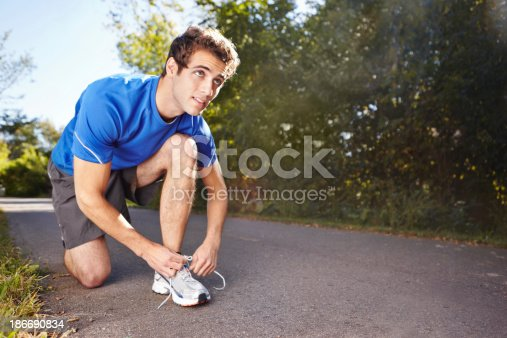 A runner tying his shoe laces on a road with copyspace