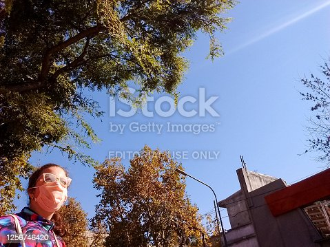 Buenos Aires (CABA), Argentina, May 19, 2020: woman with pink face mask and glasses, walking and looking to the sun in a sunny day in quarantine