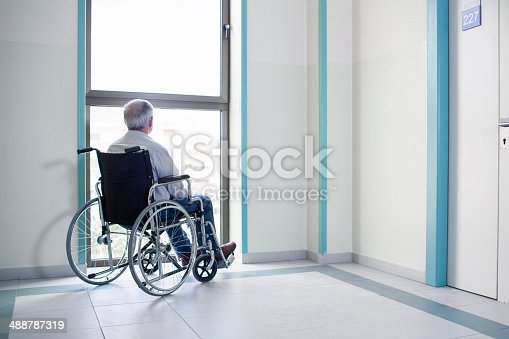 Senior man on a wheelchair looking at the view in the hospital.