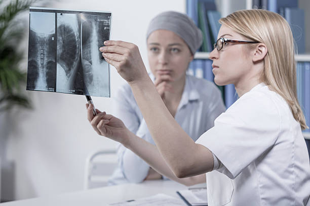 Looking at xray Young doctor looking at her patient's xray photo metastasis stock pictures, royalty-free photos & images
