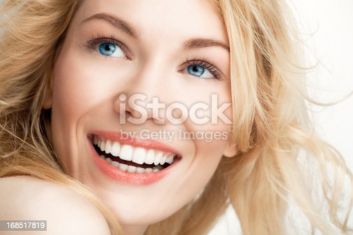 Beautiful blond, Caucasian woman smiling and looking away.