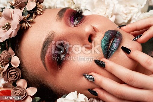 Beautiful brunette fashion model with strange makeup posing on flowerbed surrounded by plants and fruit, looking away