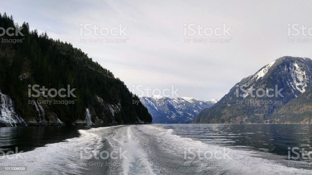 Looking behind the boat, wake and wash, coastal mountains, hazy sky stock photo