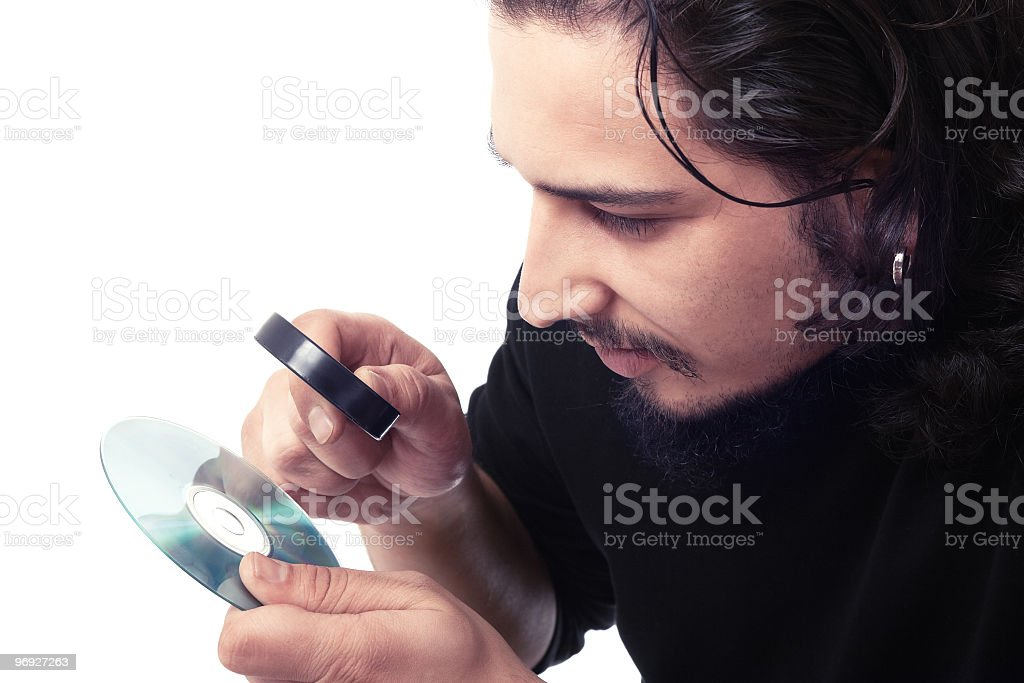 looking closely at dvd with a magnifying glass royalty-free stock photo
