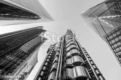 Highly detailed abstract wide view up towards the sky from extremely low angle in the financial district of London City and its ultra modern contemporary buildings, including: Willis towers Watson, the Cheese grater, the Scalpel building on Lime street and the Lloyds building originally built in 1928 (design by R. Rogers), demolished and reconstructed and opened by Queen Elizabeth II in 1986.   London is the world's greatest foreign exchange market in the district.   Shot on Canon EOS R with 14mm wide angle prime lens. Monochrome edit in Black and White, image is ideal for background with high contrast.