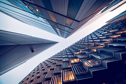 Highly detailed abstract wide angle view up towards the sky in the financial district of London City and its ultra modern contemporary buildings with unique architecture. Shot on Canon EOS R full frame with 10mm wide angle lens. Image is ideal for background. Toned image.
