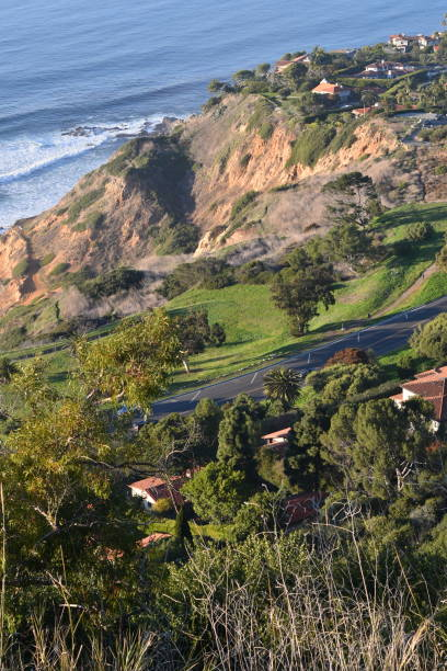 looking down a hillside vista to the ocean below - steven harrie stock pictures, royalty-free photos & images
