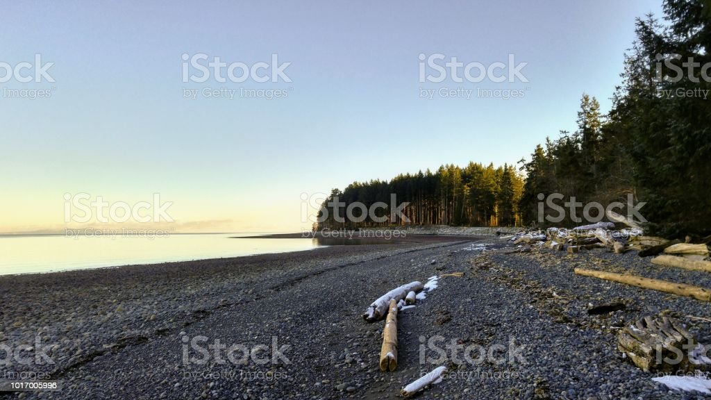 Looking down a pebble beach in late winter by the ocean stock photo