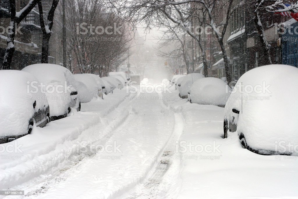 Looking down a road full of snow covered cars  stock photo