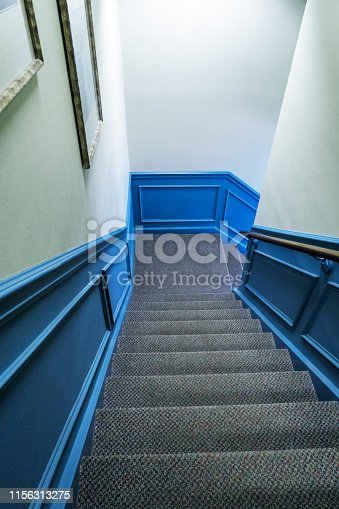 Looking down a steep carpeted staircase from the top step toward the corner landing where it turns to the right.