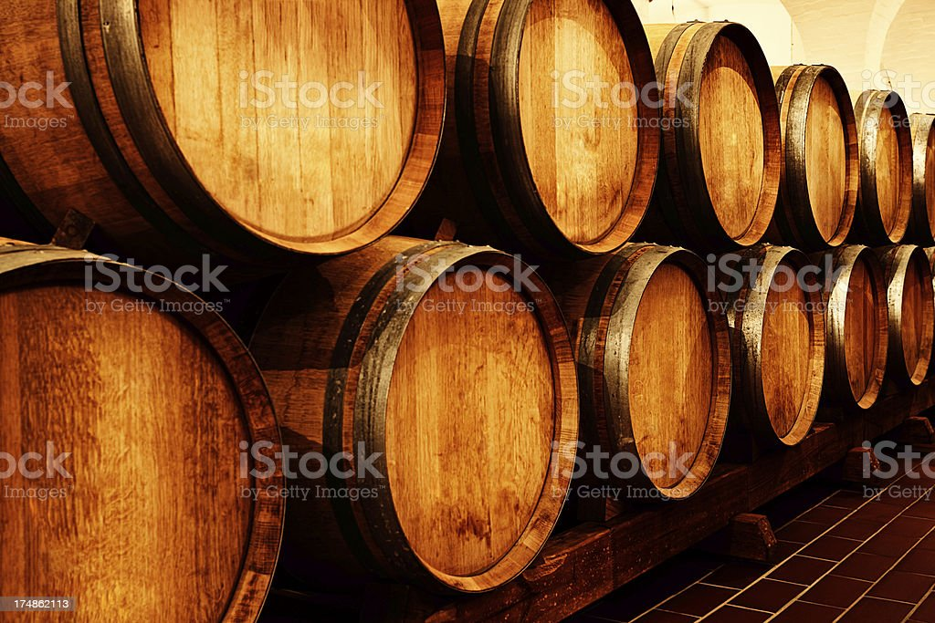 Looking down aisle of oak wine barrels in winery cellar royalty-free stock photo