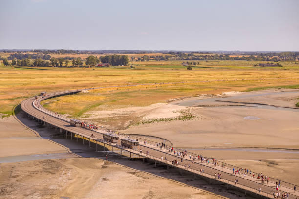 Looking down along Pont-Passerelle many tourists leave and arrive by foot with others travelling by the free tourist shuttle bus service which takes you to Mont Saint-Michel. stock photo