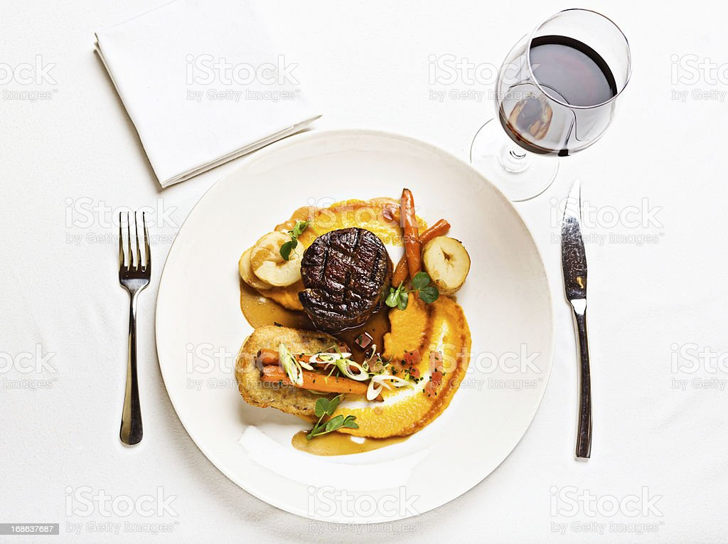 Looking down at delicious steak meal served with red wine stock photo