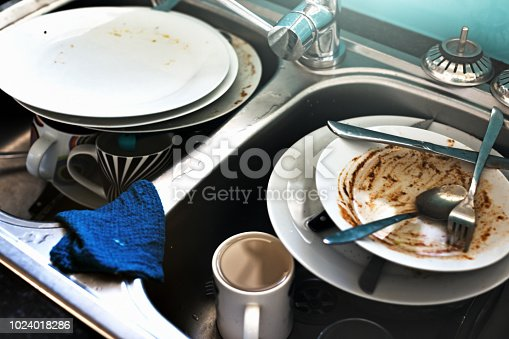 Time to do some washing up: a double sink has both sides crammed with dirty dishes.