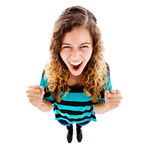 Looking down at excited young woman cheering, her fists clenched An exaggerated high-angle view of an excited young woman looking up, fists clenched and cheering. Isolated on white. Fish-eye lens exaggerates the perspective. fish eye lens stock pictures, royalty-free photos & images