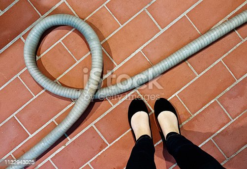 High-angle look at a woman's feet next to a coiled piece of tubing, possibly a hose or vacuum cleaner part - on brick paving.