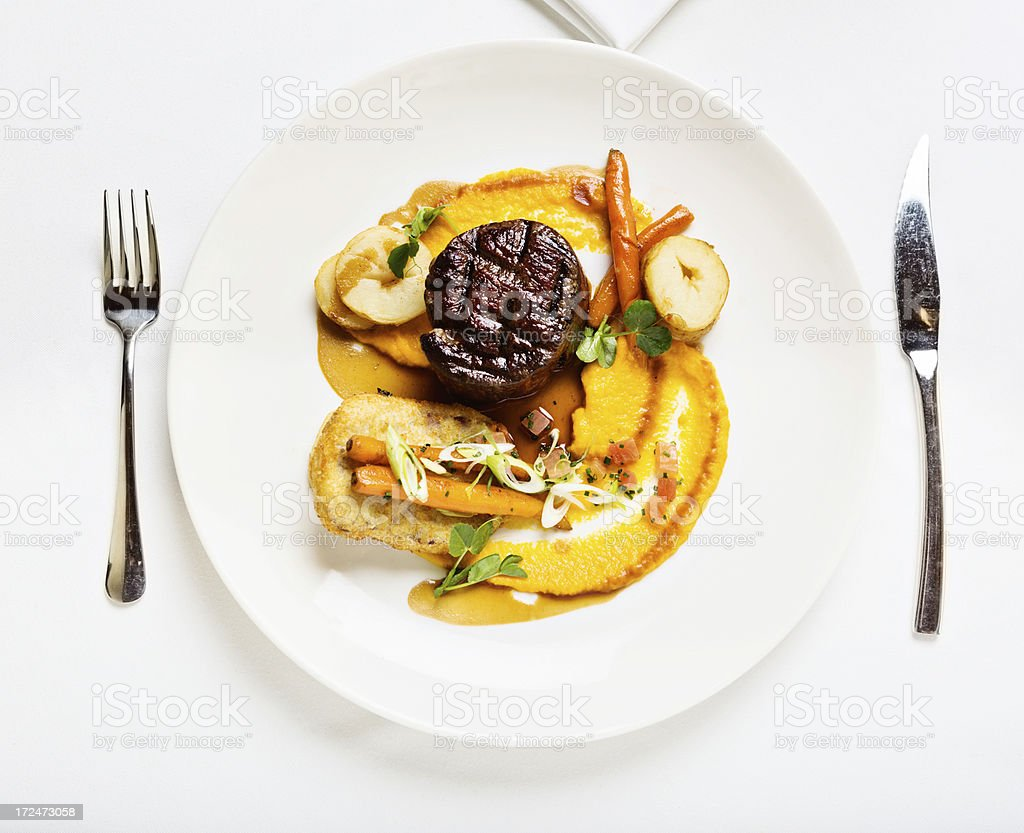 Looking down at gourmet meal of fillet steak with vegetables stock photo