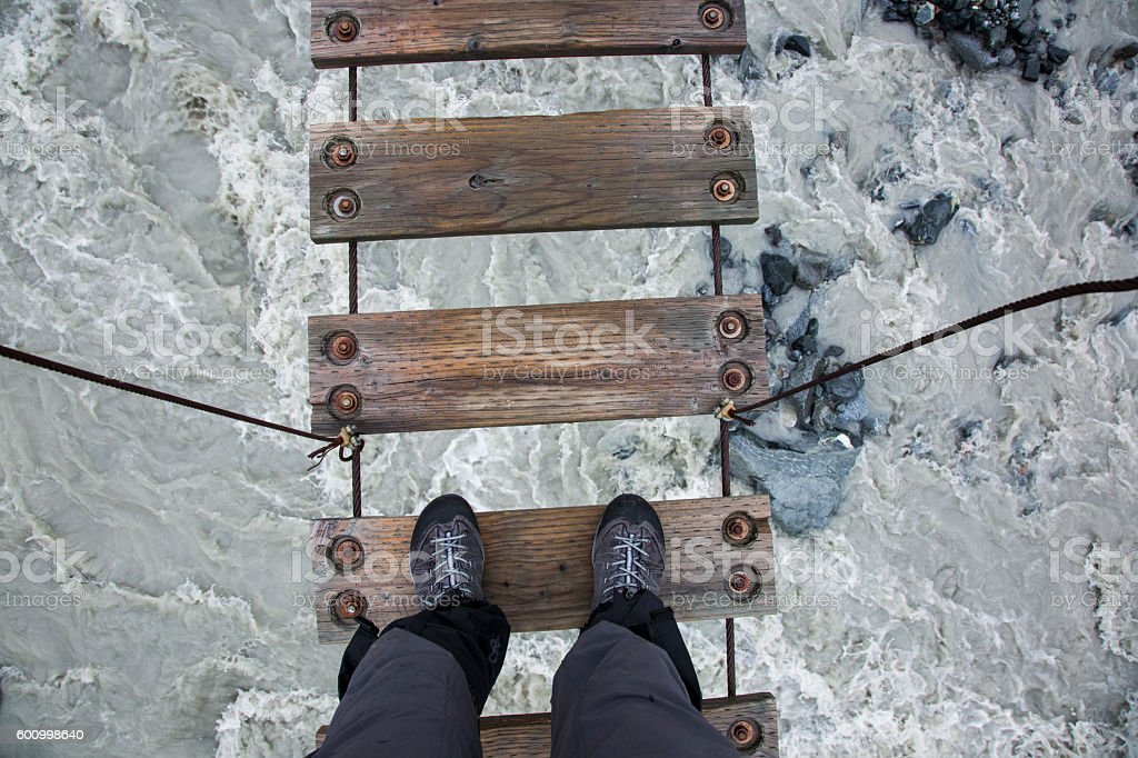 Looking Down at Hiking Boots Standing on Suspension Bridge stock photo