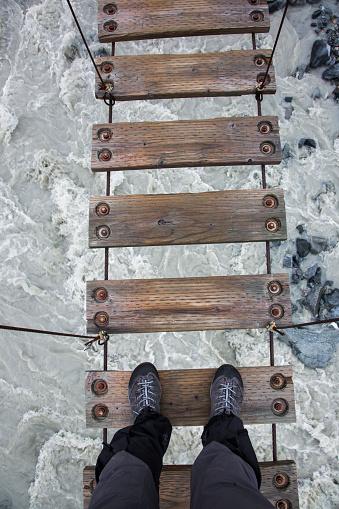 Looking Down at Feet on Dangerous Wooden Footbridge with River and Rocks below
